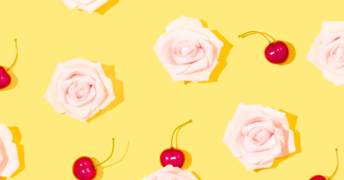light yellow backdrop with light pink roses and red cherries