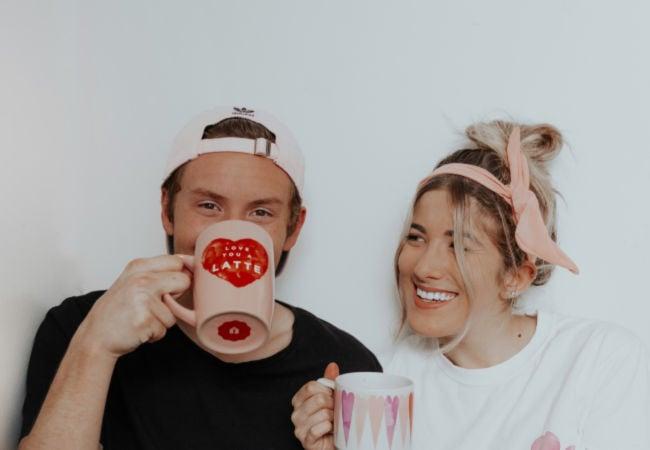 cute couple, girl smiling at man drinking from heart mug