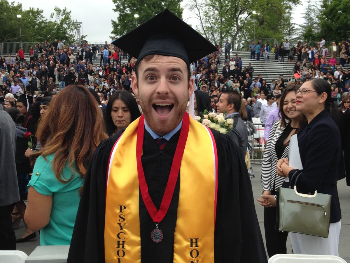 graduating college guy with an excited look on face
