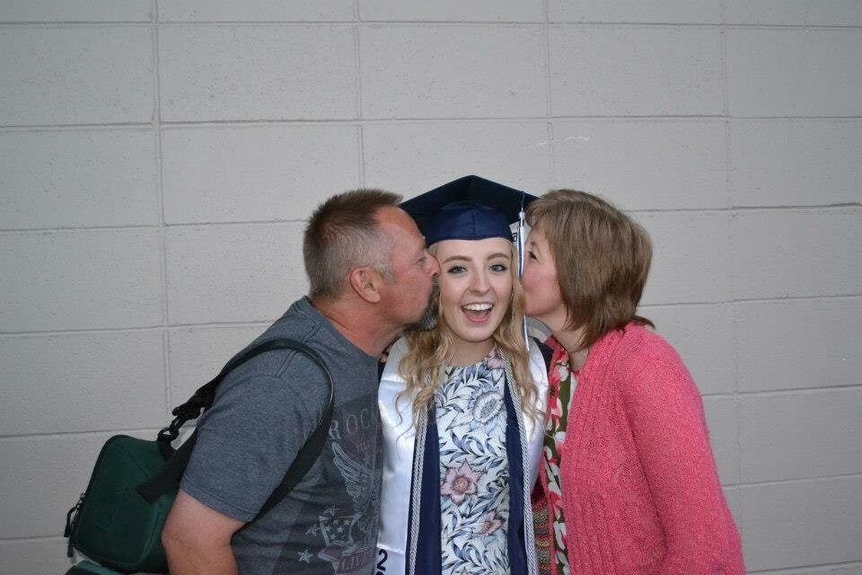 graduating college girl being kissed by parents on both sides