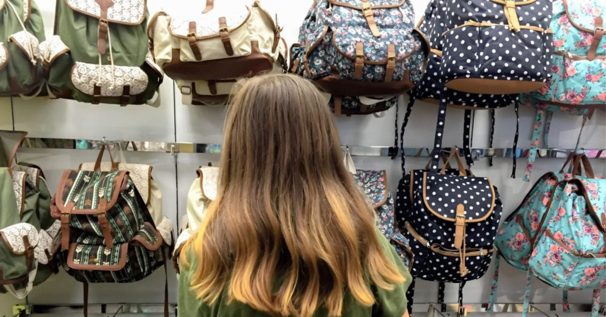 woman shopping for college backpacks and trying to decide which is cutest