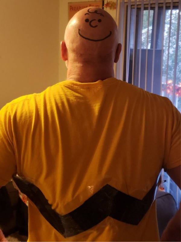 charlie brown's face drawn on bald man's head, he's wearing a yellow shirt