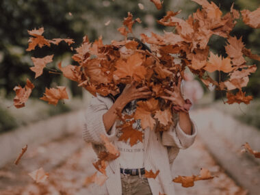 woman tossing crunchy fall leaves into the air