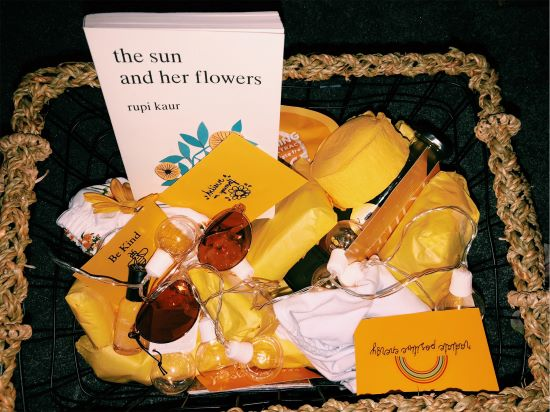 wicker gift basket with a book, sunglasses, rainbow pin and more yellow things