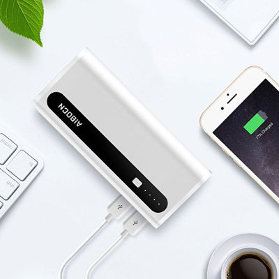 a white and black portable charger charging a phone