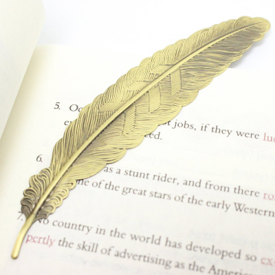 gold colored metal bookmark shaped like a feather - practical gift idea