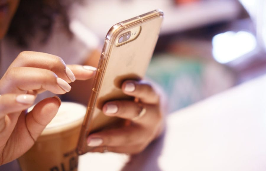close up side view of woman with manicured nails scrolling on her phone
