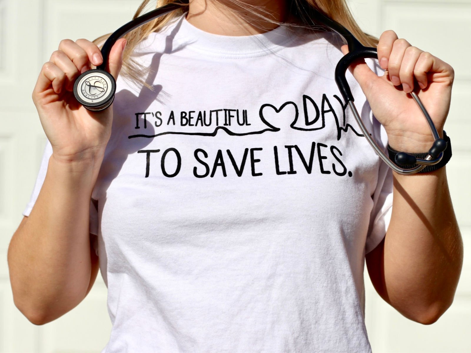 """nurse graduate wearing shirt that says, """"it's a beautiful day to save lives."""" and holding stethoscope"""
