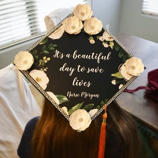 """grad cap decoration with white flowers and quote, """"it's a beautiful day to save lives - Nurse Morgan"""""""