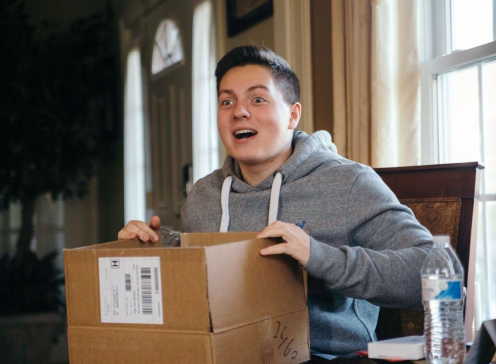 guy college student excitedly opening a care package gift