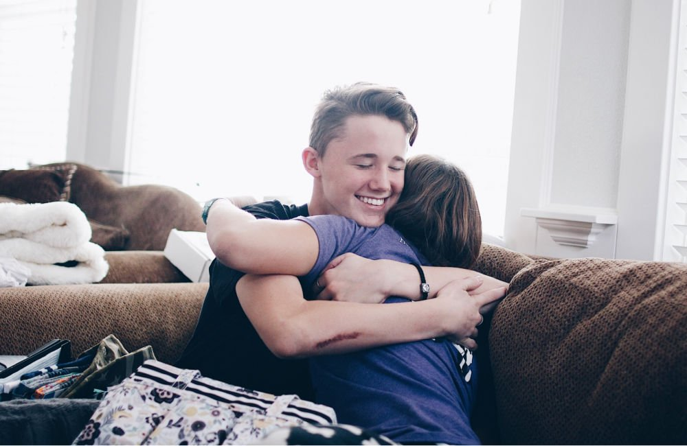 college guy with a big smile on his face hugging woman