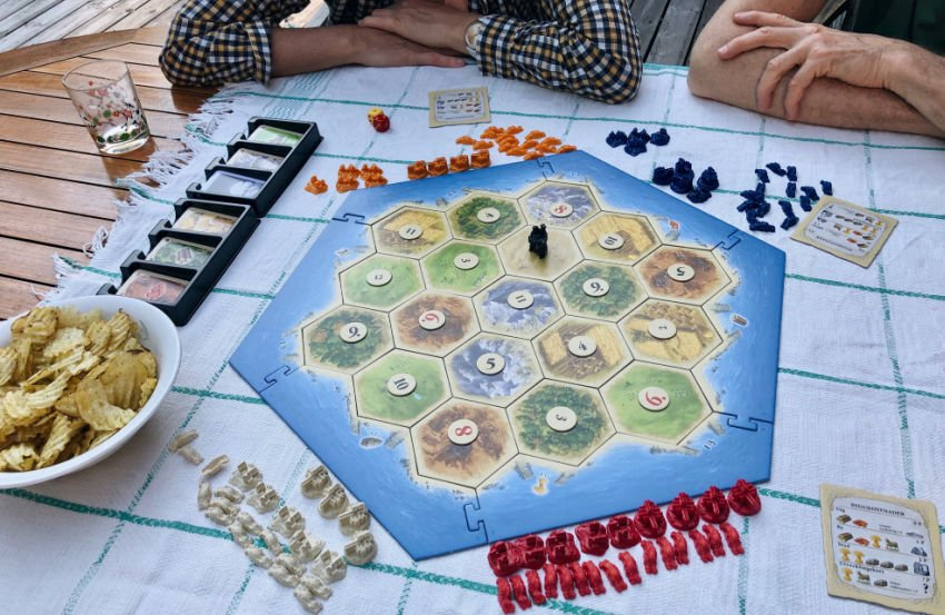 group playing Catan board game